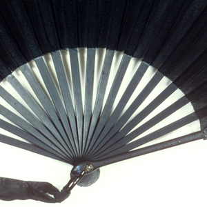 Pleated mourning fan. Black silk crepe leaf. Black painted wood guards and sticks are inlaid with round black spangles. Guards cut à jour in a strapwork design of interlacing ovals and hexagons. Horn washer and metal loop at the rivet with black silk ribbon.