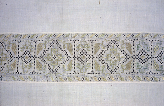 Oblong table cover of white linen with cutwork bands across the ends in simple geometric patterns and highly stylized embroidered designs in tan and blue-green. Narrow border, half inch, of cutwork and simple embroidered design surrounds the entire cover. Narrow looped fringe in the same tan and blue-green trims the piece.