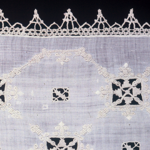 Cover with a detached arrangement of square designs of cutwork connected with white embroidered lines forming a trellis pattern. Squares framed in white embroidered design in spear-shaped patterns. Edging of pointed bobbin lace.