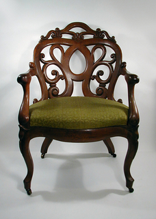 Armchair with shaped openwork back, curved in plan; serpentine arms join back to scrolled front of seat; cabriole front legs, curved and splayed rear legs, all fitted with castors. Seat upholstered in green and cream colored fabric.