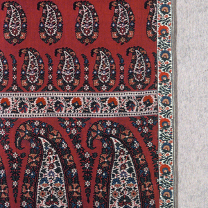 "Long scarf of crimson silk twill brocaded in multicolored cotton with deep end borders of a horizontal row of large close-set ""cones,"" stylized floral guards bands top and bottom) and smaller detached ""cones"" in close-set horizontal rows on body of scarf. Silk and cotton floral galloon applied up long sides, which have been cut."