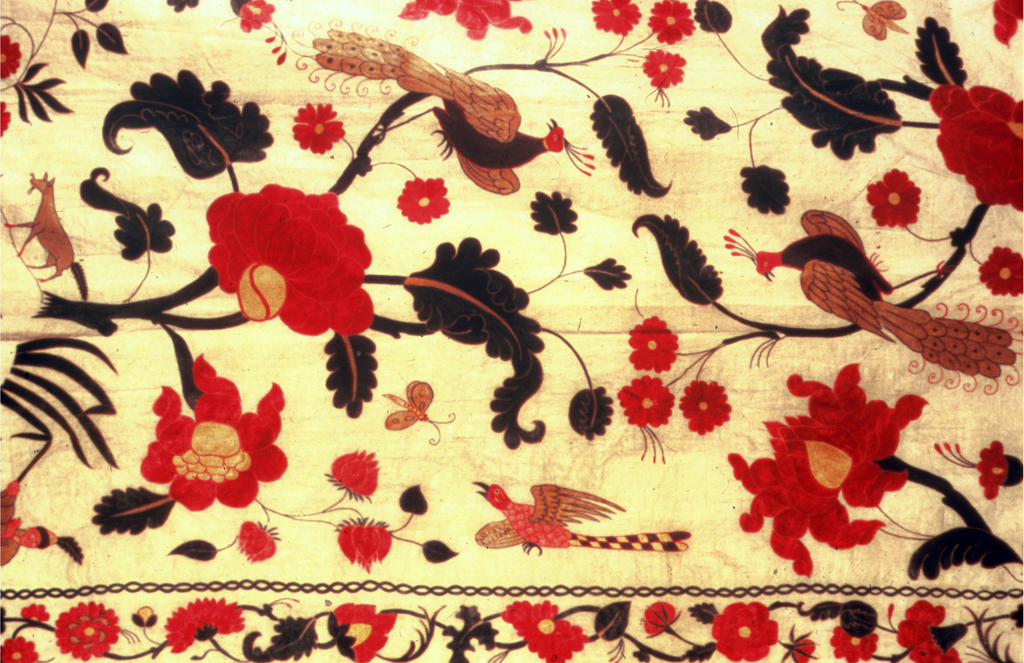 The coverlet is comprised of three breadths of fine undyed cotton plain weave, with very fine silk chain-stitch embroidery in brown, violet, two shades of blue, yellow and two shades of pink, lined with plain cotton.  The design is similar to 1953-123-1, but composed for a coverlet: the flowering branches fill the field, but the rockery and its figures appear at the bottom and reversed at the top. In the center, a medallion filled with a miniature pattern of flowering vines framing a pair of plying birds. The same elements are used in the four corners, but with a single bird. The whole is framed by a wide border and two narrow guard borders with flowering vines. At one end the border is largely missing. The design is simplified in detail and bolder in color than the chintz.