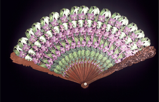 Brisé fan.  Carved wood blades painted from base to tip with a stylized design of violets and snow-drops; the guards are carved with the same design. Connected with a painted silk ribbon; mother-of-pearl washer.