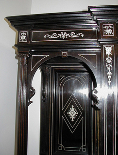 """Rectangular cabinet with slightly projecting central section consisting of four-shelved cupboard concealed by vertical double doors over shallow horizontal drawer. Side section consists of open upper shelf with fluted corner colonette over four small drawers over single door. Stepped cornice, molded base, six ball feet. Extensive ivory inlay on doors, drawers, framing, sides with most important motif being a female figure with attributes on each center door. Ivory drawer pulls; drawers lined with dark red velvet; key. On each center door, inside top, ivory plaque with name: """"Soubrier.""""  A- base B- back panel C-right cabinet  D-left cabinet  E- right door F- left door G- drawer  H- top  I - key  Also two small panels on 5th fl. 11-B"""