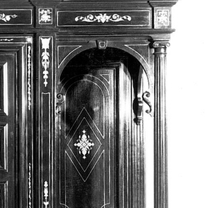 "Rectangular cabinet with slightly projecting central section consisting of four-shelved cupboard concealed by vertical double doors over shallow horizontal drawer. Side section consists of open upper shelf with fluted corner colonette over four small drawers over single door. Stepped cornice, molded base, six ball feet. Extensive ivory inlay on doors, drawers, framing, sides with most important motif being a female figure with attributes on each center door. Ivory drawer pulls; drawers lined with dark red velvet; key. On each center door, inside top, ivory plaque with name: ""Soubrier.""  A- base B- back panel C-right cabinet  D-left cabinet  E- right door F- left door G- drawer  H- top  I - key  Also two small panels on 5th fl. 11-B"