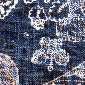 Fragment of resist-printed linen, with a pattern of left-facing bird with outstretched wings seated on baskets of flowers. Design in white on faded blue ground.