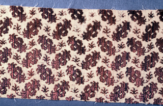 Small symmetrical figure with leaf curving from lower end closely set at right angles, in stie mauve and blue voided cut and uncut velvet on cream cloth ground originally run through with metal strips.