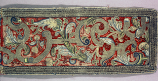 Horizontal panel, possibly part of a valance, of red velvet heavily worked in gold thread and colored silks. Graceful flowering vines curve through asymmetrical arrangement of joining S-curves. Flowers in shaded effects, in blues, yellows, greens, and soft rose and outlined with gold thread. The S-curves and bands in gold couched to give a block design. Wide border of gold couched over cord to give raised effect.