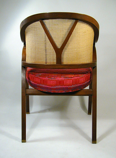 Dark brown wood frame with roughly ovoid curved and caned back and arms; Y-shaped wooden support connecting horizontal frame elements. Straight front legs rising to form arm supports; splayed rear legs curved forward at top to meet front legs. Seat upholstered in warm-toned woven fabric of red, orange, and purple hues.