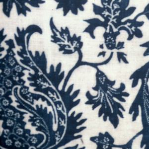 Coarse white cotton printed in blue in a design of scrolling foliage and pomegranate arranged in an allover pattern. Throughout the design is furthur ornamented by small white dots emphasizing the line of growth or providing extra interior decoration. No selvages.