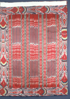 Bed cover or suzani in cream-colored cotton embroidered with colored silks and lined with warp-printed silk. Small red carnations fill the field, surrounded by a wide border of large, circular red flower heads and scrolling vines. Lined with two different warp print silks, a satin stripe and a ribbed silk with a figural design.