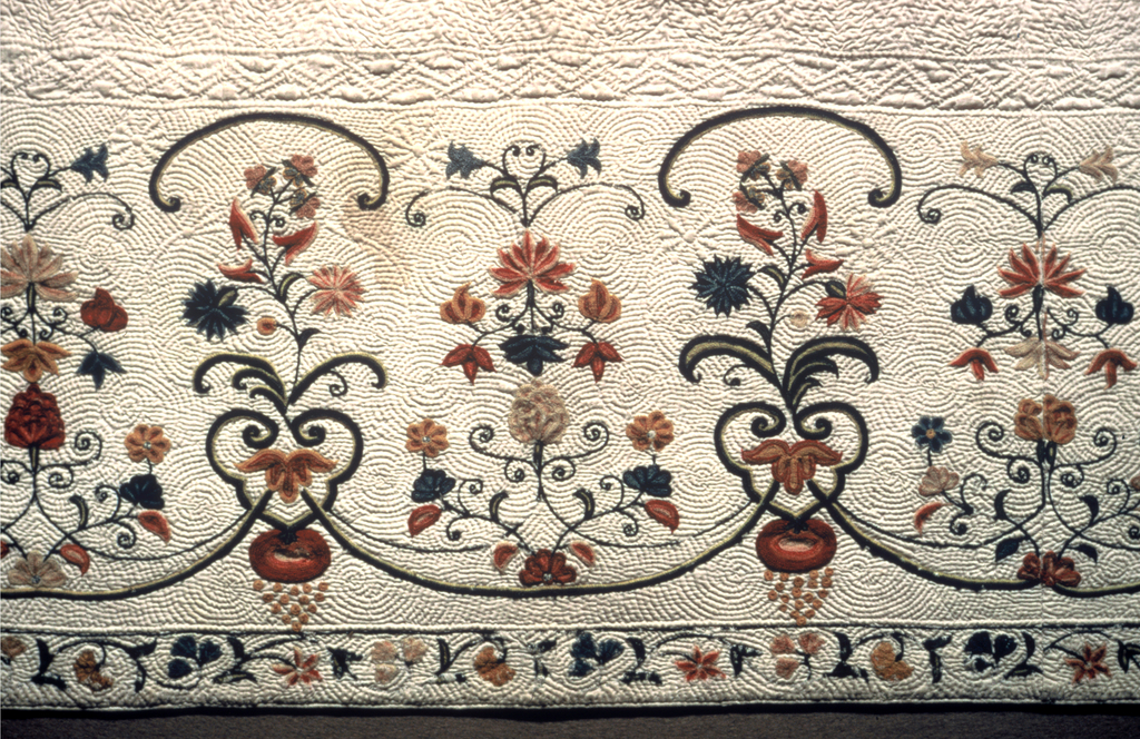 One half of a woman's skirt, white cotton, backed with linen, quilted; wide border at bottom embroidered in polychrome wool. Border design: Quilting, small circular pattern, spiral ending in flower heads. embroidery, arrangement of alternating flower sprays, formally arranged, connected below with curving lines, and with shorter curves above, suggesting broken enframement. Reds, blues, yellows, pinks, lavendar, drab. Many flowers and leaves outlined in different colors. Narrow  guard border below, of trailing vine. Stitches, chain and herring bone. Note that the quilting is worked through the lining, but embroidery is entirely on surface. Body of skirt is quilted in simple zig zag, perpendicular. Pocket hole at top, now stitched together. Stitches using wool: chain, buttonhole. Quilted with linen thread through back layer of sheer cotton plain weave with inner layer of cotton wadding in upper section and in border band cotton cord inserted through back between rows of stitches.