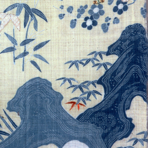 Detail of a landscape with rocks, various leafy stalks and flowering branches in shades of blue on a cream ground. A few small areas are printed in a brownish shade with white dots or completely reserved in white. Small area of couched metallic thread and orange and green silk embroidery.