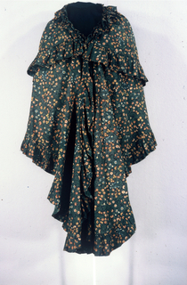 Tiered and ruffle-edged cape of cotton printed with a multicolored floral pattern on a black ground.