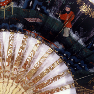 Pleated fan. Black glazed paper leaf painted with gouache. Obverse: a Chinoiserie scene of figures in a garden; gilded swags. Reverse: black ground with 3 flower sprays. Sticks of carved, incised, pierced and painted ivory showing figures and scrolls. Glass stone at the rivet.