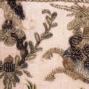 Cream-white border embroidered in gold with yellow, green, blue and white silk. The design shows a version of the Triumph of Cupid. The god, crowned and with arrows in one hand, stands in an enormous chariot drawn by a unicorn. At the rear, behind Cupid, appears a figure holding golden reins. An owl and eagle perch on the end of the chariot. The unicorn is ridden by a winged boy. The figures are worked in white silk with black for eyes. Colored silks used for crowns. Chariot is in fine couched gold with heavy surface stitches for wings and reins. Along top and bottom is a narrow guard border with a design of leafy vines.