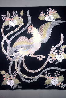 Bedcover made from five breadths of narrow fabric. Dark blue with soft shades of rose, yellow-orange, pale green and gray-violet. Design shows a large bird with widely-spread wings, long tail feathers and foliage. It is known as the Hou-ou Bird and the Paulownia Tree. The colors, now faded, were put in by hand after the ground was printed. The outlines of the bird's wings and lines in the feathers are reserved in white.