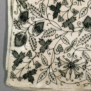 Oblong pillow cover of fine linen, embriodered in black silk. A design of scrolling stems and flowers originates in the center and flows, symmetrically left and right. Thin vine stems scroll to frame clusters of honeysuckle, strawberries (?) and leaves. A cluster of leafs and berries forms each corner. The vine stems and outlines of flowers and leaves are in a twisted stitch forming a fine cord; leaves and blossoms ornamented with many diaper fillings in running and cross-stitch. The bottom edge shows remains of black silk handstitch. On reverse at one end, the top is longer than backing, and was apparently where pillow slipped in.