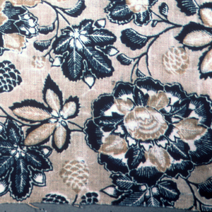 Allover pattern of flowers and seed pods in deep blue and tan on a lighter tan ground. Touches of white.