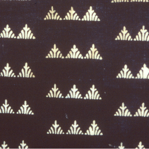 Small design of triangles joined in lines of two or three reserved in white and closely spaced on the dark blue ground. Imitation of Japanese leather design. Two selvedges continuous with ground.
