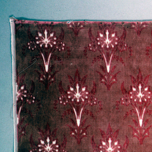 Upholstery weight cotton velvet with a design of regularly spaced symmetrical floral sprays in two shades of coral with touches of white where the backing fabric shows through.