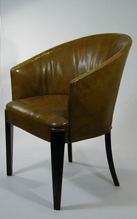 Curved back semi-circular armchair with armrests continuous with the chair's concave form.  Four wooden legs; back two tapering and swinging outwards as they reach the ground.  Chair, armrests, chair's back, and chair's seat are upholstered,