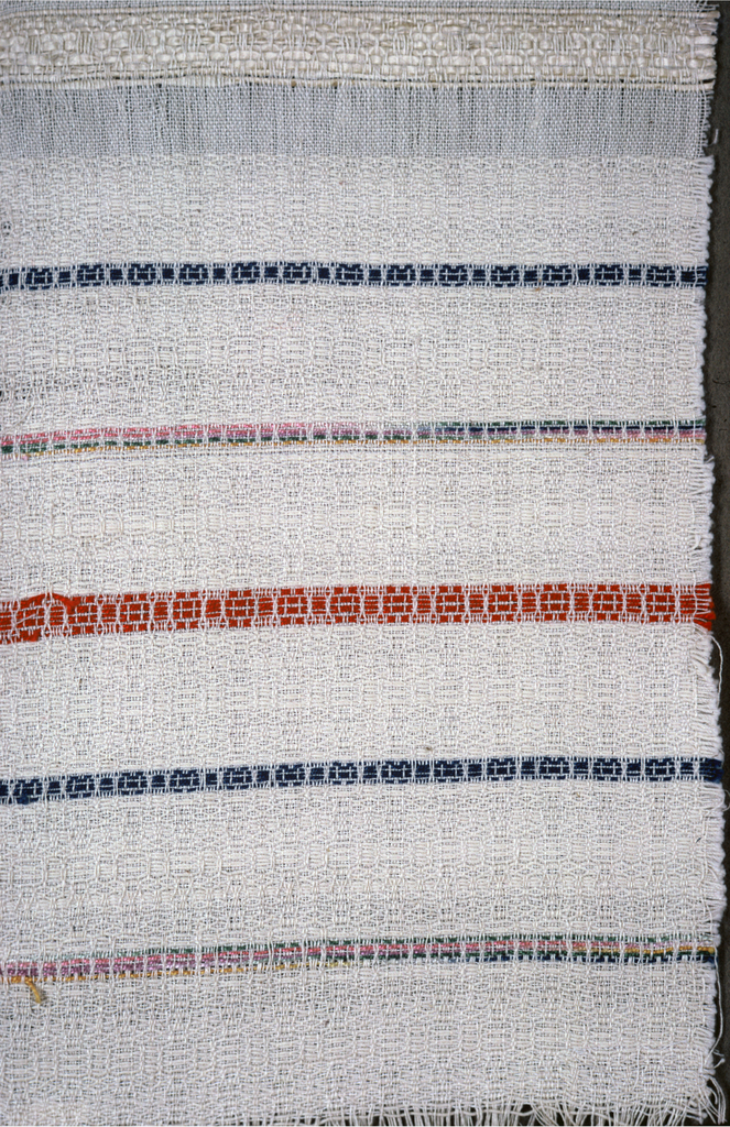 Textured off-white ground with narrow lance strips of red, blue and grouped pastels. Warp fringe and one selvage edge continuous with ground.
