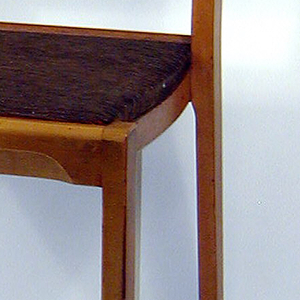 Two identical stacking side chairs with wide horizontal back splat, straight, rectangular front legs joined by rounded members that span the length of each seat front. Seats covered in woven fabric of black, brown, and metallic silver threads.