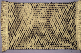 Table mat in dark yellow and dark brown has a zigzag pattern and warp fringe at both ends.