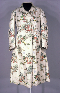 Coat of off-white compound weave silk, with multicolored silk brocading of a hunting scene and landscape.