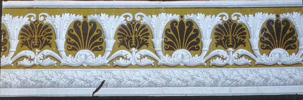 Repeating motif of stylized acanthus scrolls taking shape of cornucopia. Each pair of acanthus contains a palmette of anthemia motif. A band of foliate rope runs along bottom edge. Printed in grisaille and black  with green flock.  H# 320