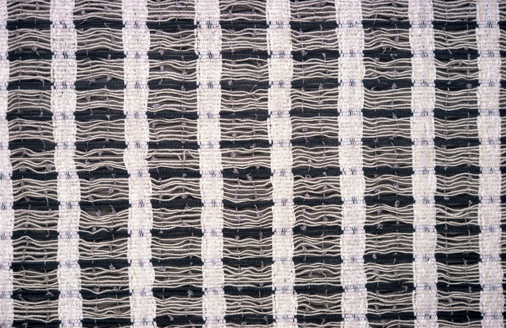 Widely spaced warp in groups of white and gray, white chenille weft is woven in strips, leaving large open spaces. Two lavender nylon picks are shot through in these spaces.