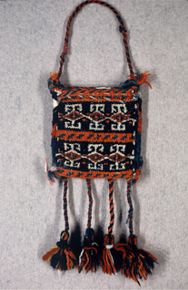 Small flat bag of handwoven wool in red, orange, black, white, and green showing a geometric pattern on one side and plain red on the reverse. Wool cord handle and long tassels hang from bottom edge.
