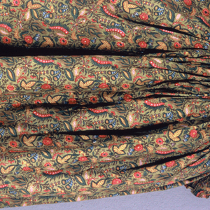 Full cape with a hood whose fullness radiates from a tight group of pleats at the back of the head. Cotton has a small-scale design of exotic floral forms in the Indian style in brown, blue, green, yellow, red and violet with small amounts of reserved white, on a dark gold ground. Bordered all around with a wide gathered band of the same fabric. Lined with coarse dark blue cotton, resist-printed with a thin white stripe.