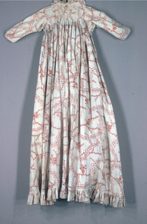 Woman's printed cotton dress, with a low neckline gathered on to a drawstring in front; across the back fullness is gathered into sewn-down pleats across the shouler blades. The dress hangs waistless to the floor, and has a small train in the back. Close-fitting set-in sleeves. Ruffle around the neck and hem edges. Pocket slits in side seams. A plain linen lining in the top forms a fitted inner bodice, with holes for lacing in front. The fabric is copper plate printed in red on a white ground, with thin meandering branches, a few clusters of small flowers, intersected by a meandering arrangement of flower buds.