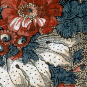 Printed fabric, quilted and lined, in the shape of a chair back. Spray of naturalistic flowers in reds and blues, foliage in brown. Background has a sprig design in light brown against a dark brown ground. Some of the blue color appears to be painted in.
