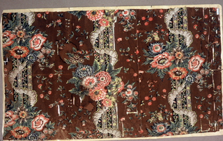 Panel of dark brown cotton printed in shades of red, brown, yellow, and green. Large floral bouquet set within garlands against floral stripes.