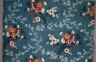 Pale blue ground with a background of a small vine pattern reserved in white, possibly by discharge. Overprinted by block in a pattern of flower clusters in red, dark brown and dark green.