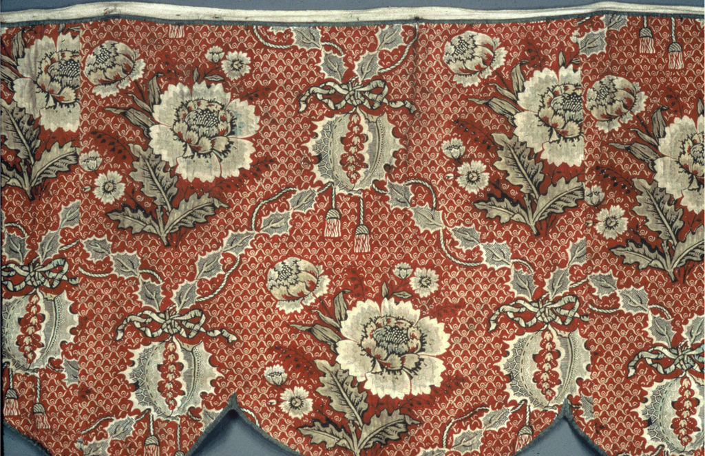Valance in a floral design consisting of a red ground with imbricated pattern in white. Large flowers clusters in white, red and dark brown with garlands of leaves in dark brown and red. With cords and tassels. Variety of picotage used in flower leaves. Leaf garlands printed with dark brown horizontal lines. Much detail outlined in black and dark brown. Faced with fragments of block printed cotton in tulip and leaf pattern in reds and dark brown.