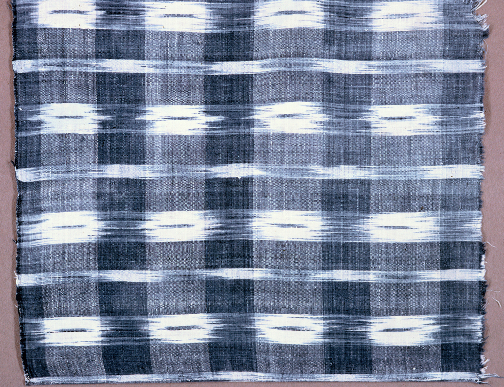 Alternating warp stripes of light blue and white intersect with blue and white weft stripes to form a large scale plaid pattern with both solid color and ikat stripes.