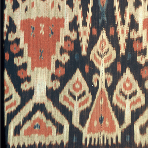 Men's ceremonial wrapper in red, brown, buff, and blue. Central section shows a patola-inspired motif (groups of diamons shaped lozenges interspersed with small circular motifs). Flanking the center on both ends is a row of birds confronted on either side of an upright blue fish; then a wide band of trees: one small with three conical branches, the other large, resembling candelabrum. The outermost bands have the bird and fish motif again. Two widths sewn together. Warp fringe (6in.) at both ends.