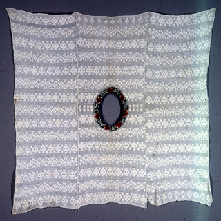 Loosely woven white cotton plain weave with geometric patterning. Three widths sewn together. Head opening in center is reinforced with band of purple cotton solidly embroidered in polychrome cottons in bold floral pattern.