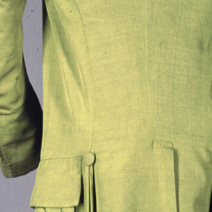 Man's suit coat in yellow-green ribbed silk lined with undyed linen. Self-covered buttons down the front, along the pocket flaps, around deep cuffs, and at top and sides of side vents. Coat has a small standup collar, no lapels, and three brass hooks and eyes for closing the front which slopes towards the sides of the body. Hangs to the knees.