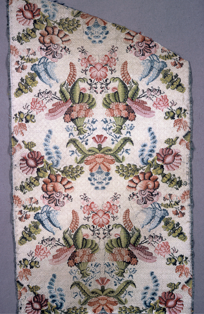 Length of cream colored silk with floral diaper patterned ground, brocaded in large allover symmetrical pattern in polychrome silk. Both selvages present.