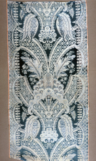 Panel of light blue and white silk with light red details. Pattern shows large scale, symmetrical repeat; fan-shaped with large leaves and branching bands. Both selvages present. Repeat 0M660 long.