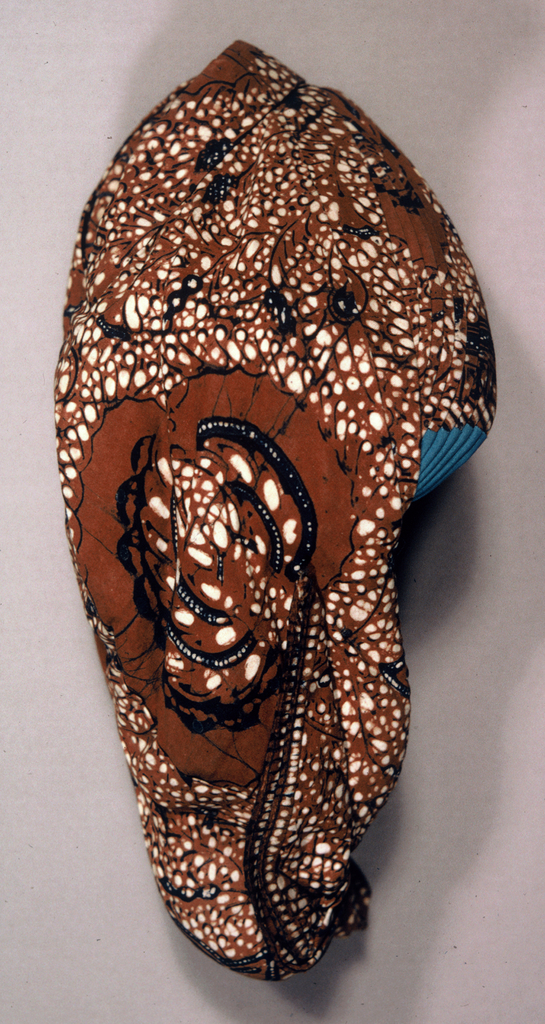Constructed cap of batik fabric. Fully lined, pleated at the front, stuffed knob at back, with bright blue inset at ears. Fabric batiked in brown, dark blue, and off-white showing sawat (two wings of Garuda, mount of Vishnu) motif among organic off-white dots on brown ground
