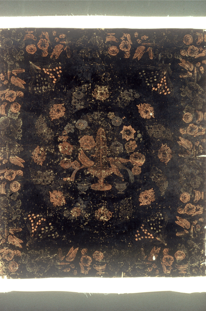 Black oilcloth table cover printed in dull red. Center has birds drinking from a fountain surrounded by a flower wreath. Border has flowers, a cup and a fountain.