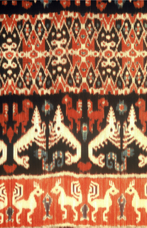 Rectangular panel with fringe at ends. Dyed in warp ikat technique in indigo blue, dark brown, red, and (reserved) white. Alternating blue and red horizontal bands with figures in white and red: rows of stags, snakes (naga), and roosters, and lobsters. Patola-inspired center band.