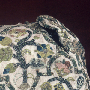 Off-white linen coif, shaped at cheek and with a point over the forehead, embroidered in gold-wrapped silk and colored silk threads in rose, green, pale green, blue and yellow. A lattice pattern in green and gold frames flowering branches, pears, peas, and grapes with many details in high relief in gold.