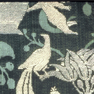 Green silk damask, brocaded in gold and rose; hunters, birds, winged figures, supporting an urn.